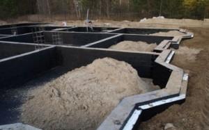 После полного завершения работ по утеплению весь периметр фундамента нужно засыпать песком, чтобы прикрыть пеноплекс