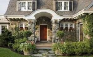 Чтобы сгладить ощущение массивности и недружелюбия, крыльцо и дом окружили большим количеством зелени