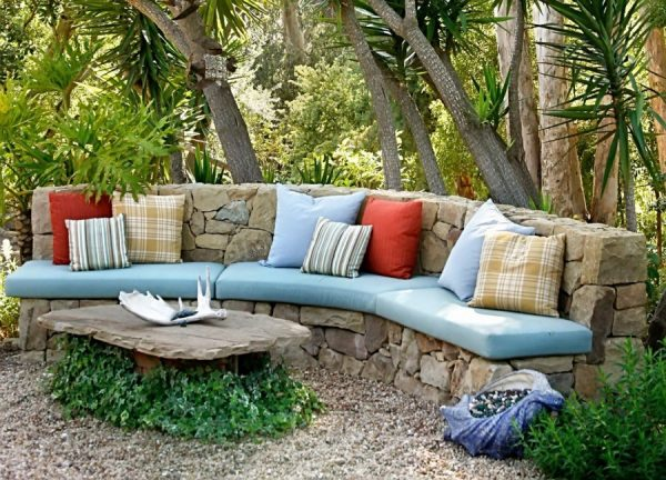 Уютный диванчик с подушками в тени деревьев