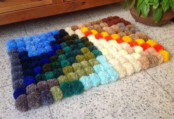 Разноцветный прямоугольный коврик из помпонов