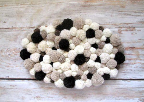 Овальный коврик из помпонов разного размера