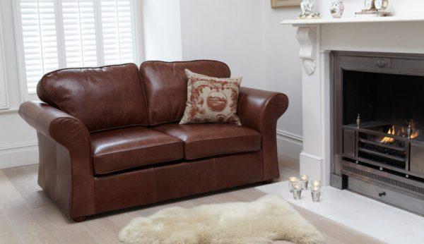 Небольшой кожаный диван у камина