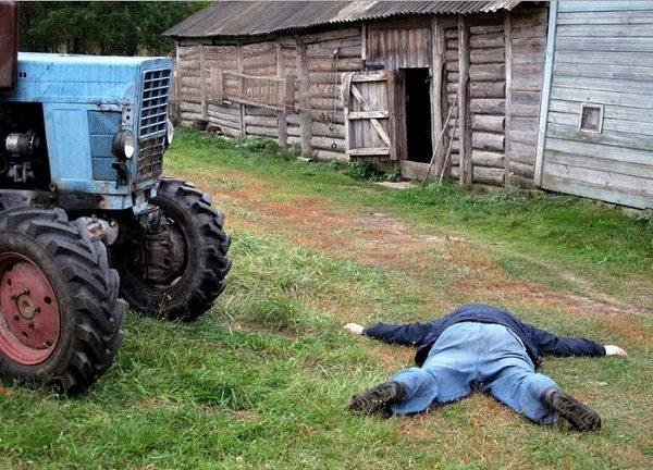 Мужчина лежит на земле у трактора